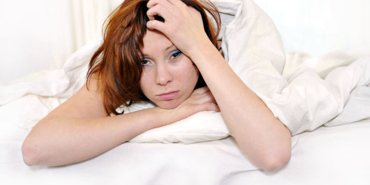 Frau liegt mit Kopfschmerzen im Bett