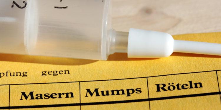 Auf einem gelben Impfpass liegt eine Spritze