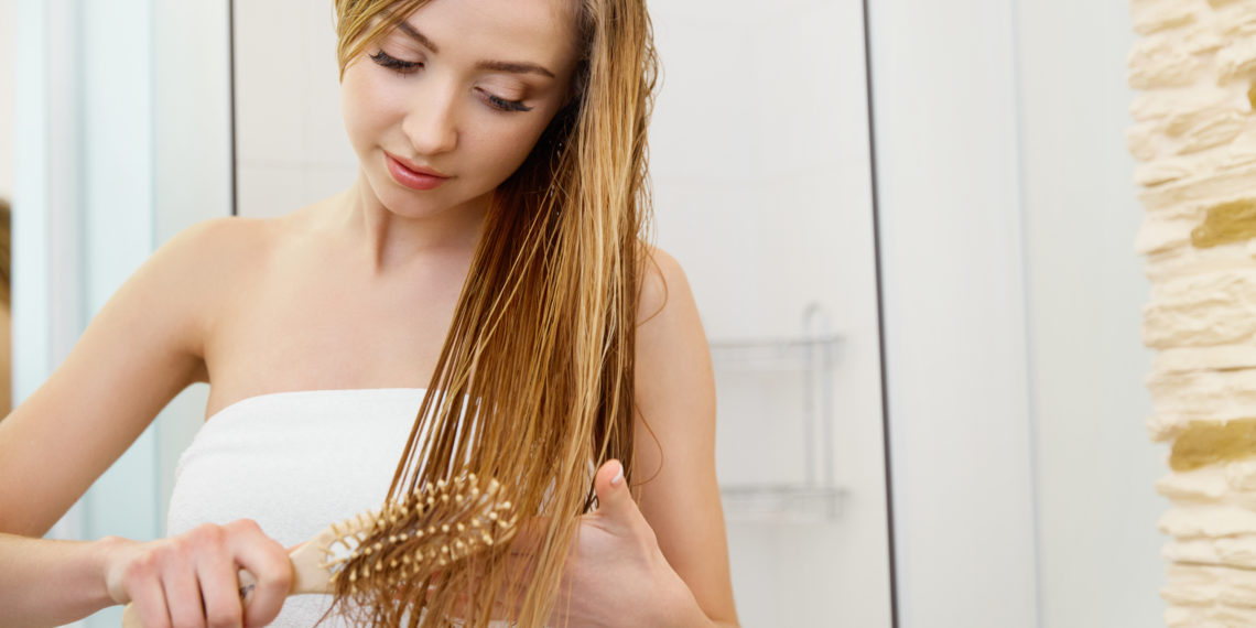 Frau kämmt ihre nassen Haare.