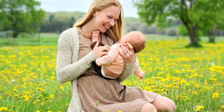 Junge Frau kitzelt ihr Baby auf einer Blumenwiese