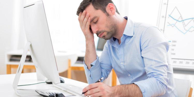 Ein Mann sitzt erschöpft im Büro und hält sich die Hand an die Stirn.