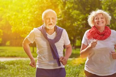 Zwei glückliche Senioren beim Jogging im Park im Sommer