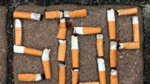 """Wort """"Stop"""" aus Zigarettenstummeln auf Pflaster"""