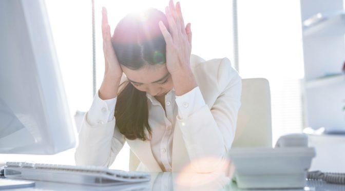 Frau im Büro hat Kopfschmerzen