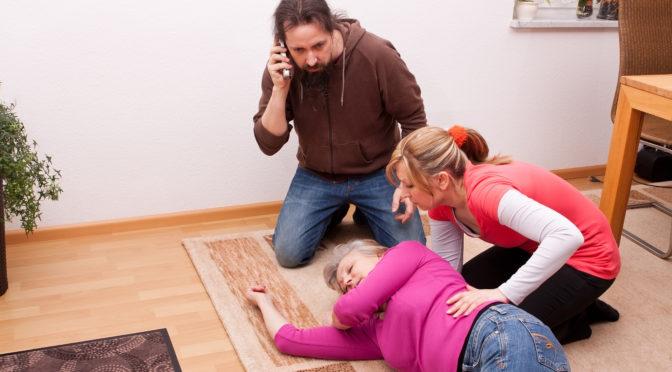 Zwei Personen leisten erste Hilfe bei einer älteren Frau