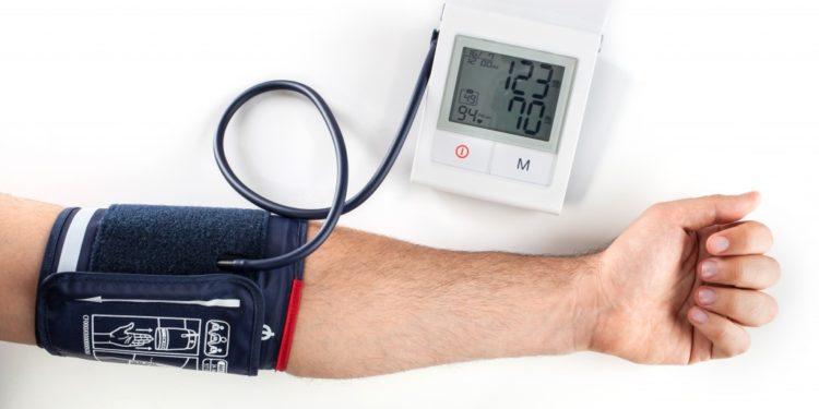 Ausgestreckter Arm mit Blutdruckmanschette und Blutdruckmessgerät