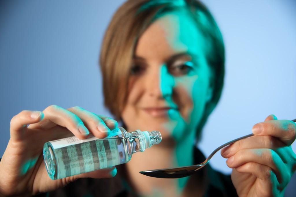 Frau mit einer Flasche Melissengeistund einem Löffel