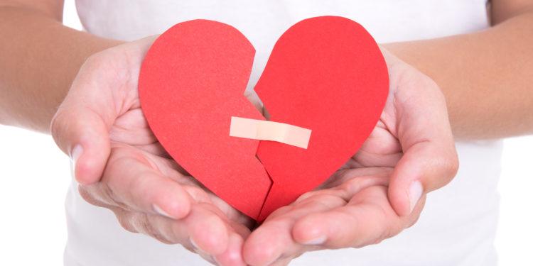 Mann hält in seinen Händen ein zerbrochenes Herz, auf dem ein Pflaster klebt