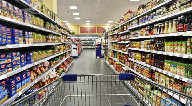 Mit einem Einkaufswagen durch den Supermarkt