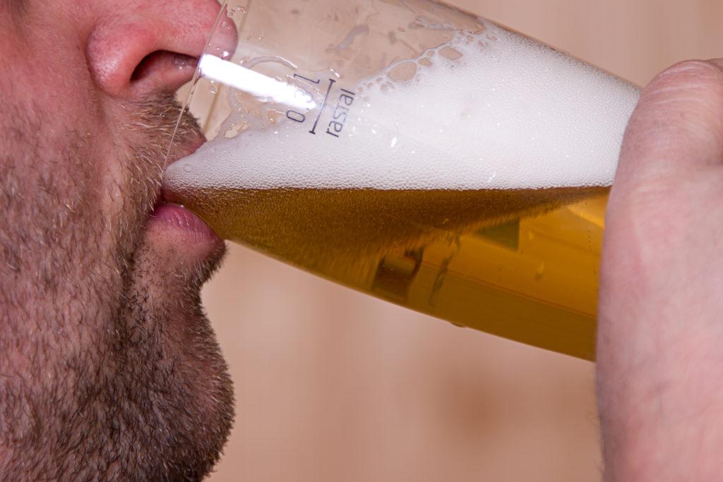 Mann trinkt Bier aus einem Glas