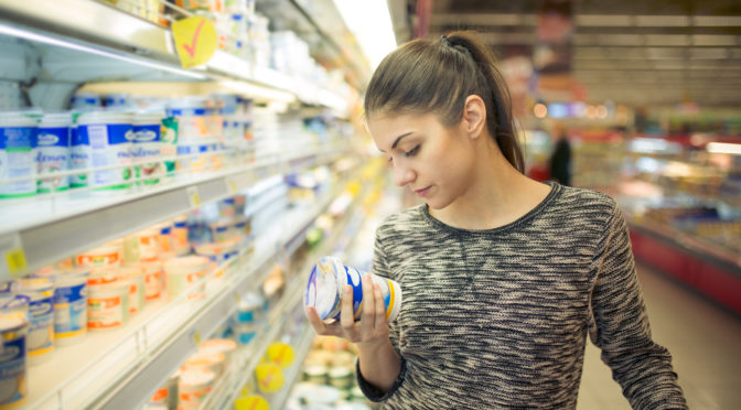 Frau liest sich im Supermarkt die Produktbeschreibung durch