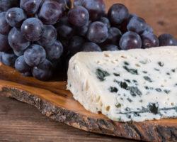 Blauschimmelkäse und blaue Trauben auf einem Brett