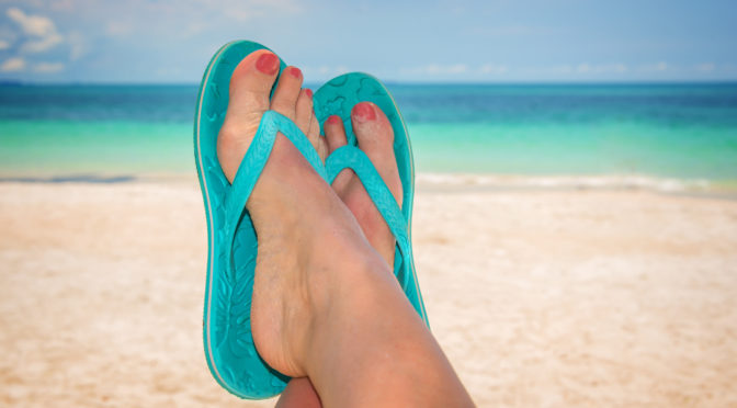 Frauenfüße in Flip-Flops am Meeresstrand
