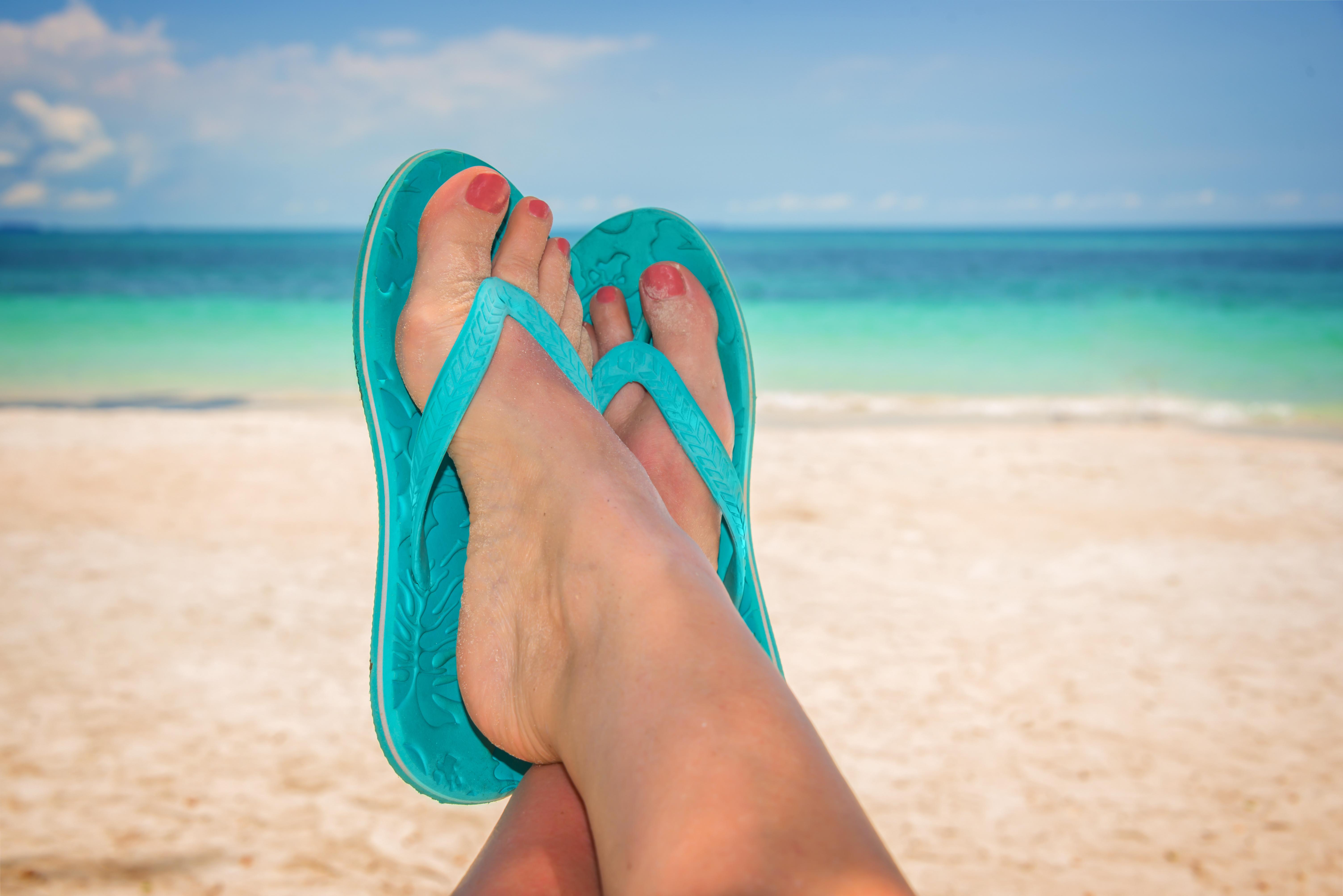 Frauenfüße in Flip-Flops am Meeresstrand