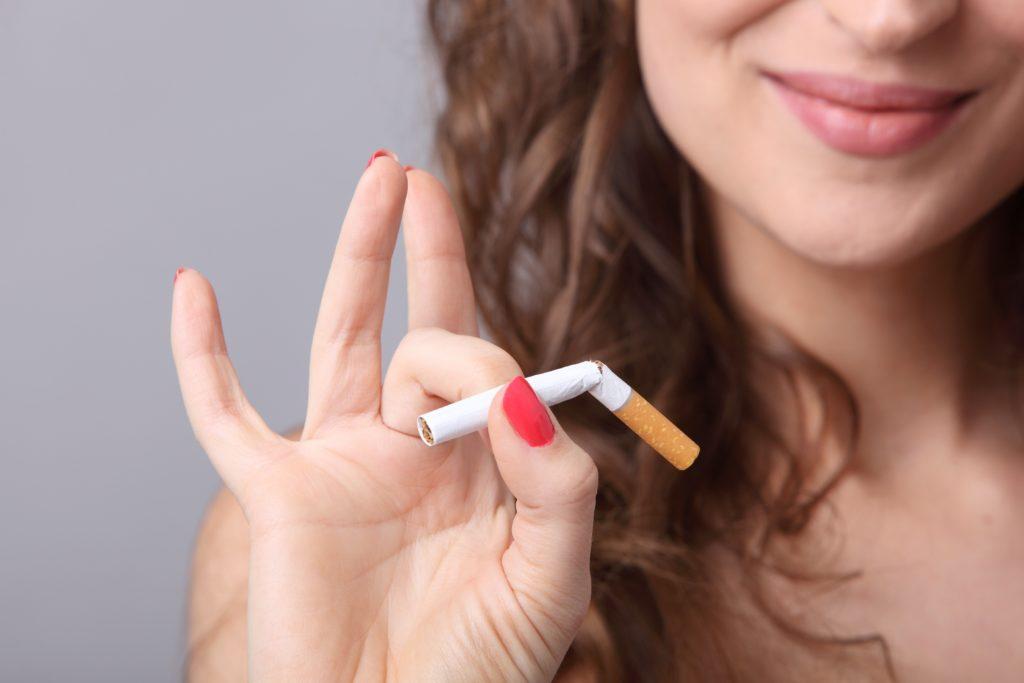 Lächelnde Frau schnippt eine zerbrochene Zigarette weg