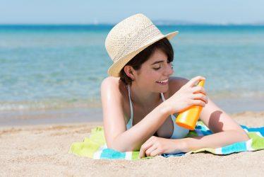 Junge Frau am Strand trägt Sonnenschutzmittel auf die Haut auf