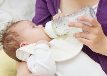 Frau füttert ihr Baby mit Milch aus der Nuckelflasche