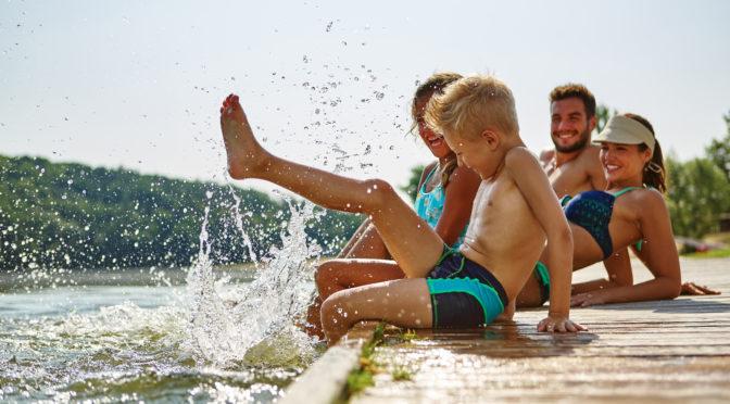Mehrere Mitglieder einer Familie plantschen im Wasser