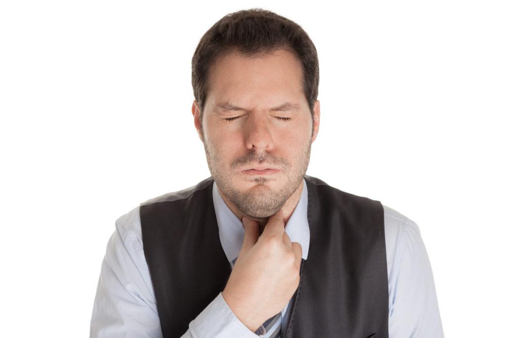 Ein Mann mit leidendem Gesichtsausdruck hält sich am Hals