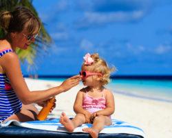 Mutter cremt ihre Tochter am Strand mit Sonnenschutzmittel ein