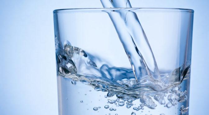 Wasser wird in ein Glas gegossen