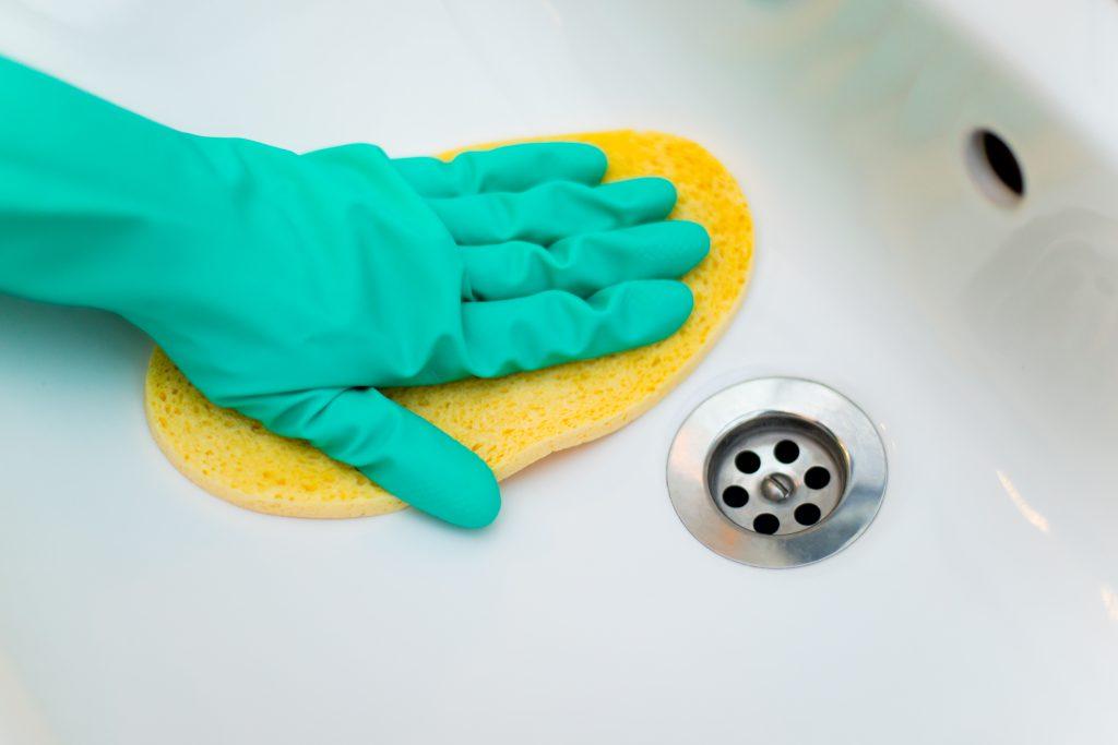 Waschbecken putzen im Gummihandschuh