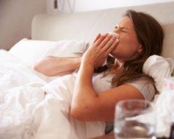 Frau liegt mit Erkältung im Bett