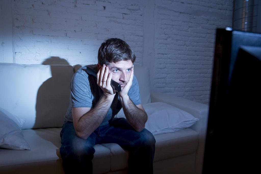Mann sitzt auf einem Sofa und starrt auf einen laufenden Fernseher