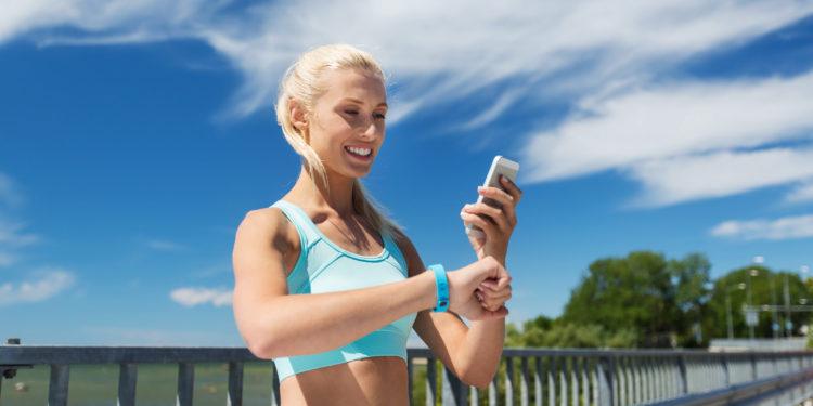 Frau mit Fitnessarmband schaut auf ihr Smartphone.