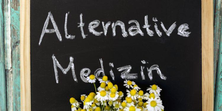 Ein Strauß Margeriten vor einer Tafel mit der Aufschrift: Alternative Medizin
