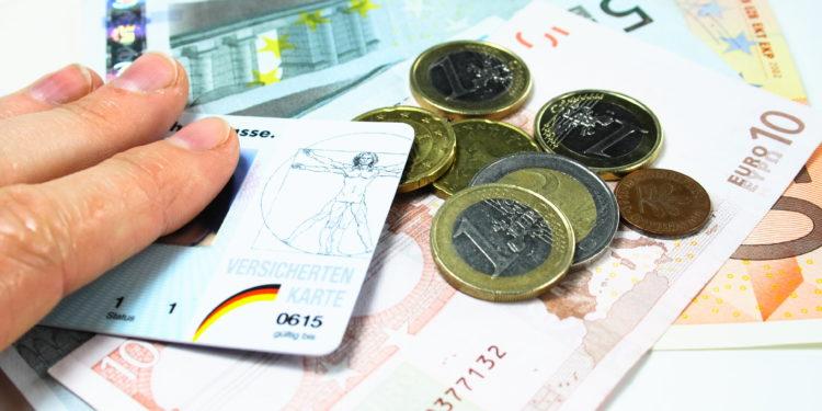 Eine Krankenversichertenkarte auf mehreren Geldscheinen und Münzen