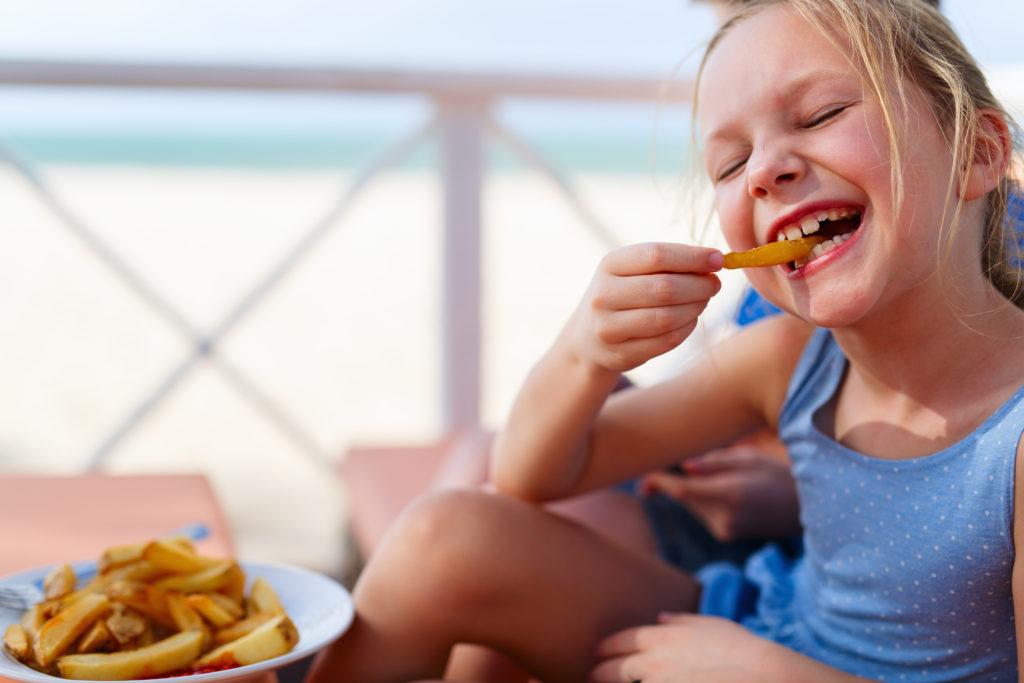 Kindern, die sich gerade Pommes oder ein Eis gegönnt haben, wird oft gesagt, dass sie mit dem Schwimmen warten müssen, weil es gefährlich ist, mit vollem Magen ins Wasser zu gehen. Was ist an der Behauptung dran? (Bild: BlueOrange Studio/fotolia.com)