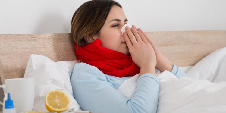Frau kuriert im Bett ihre Erkältung aus