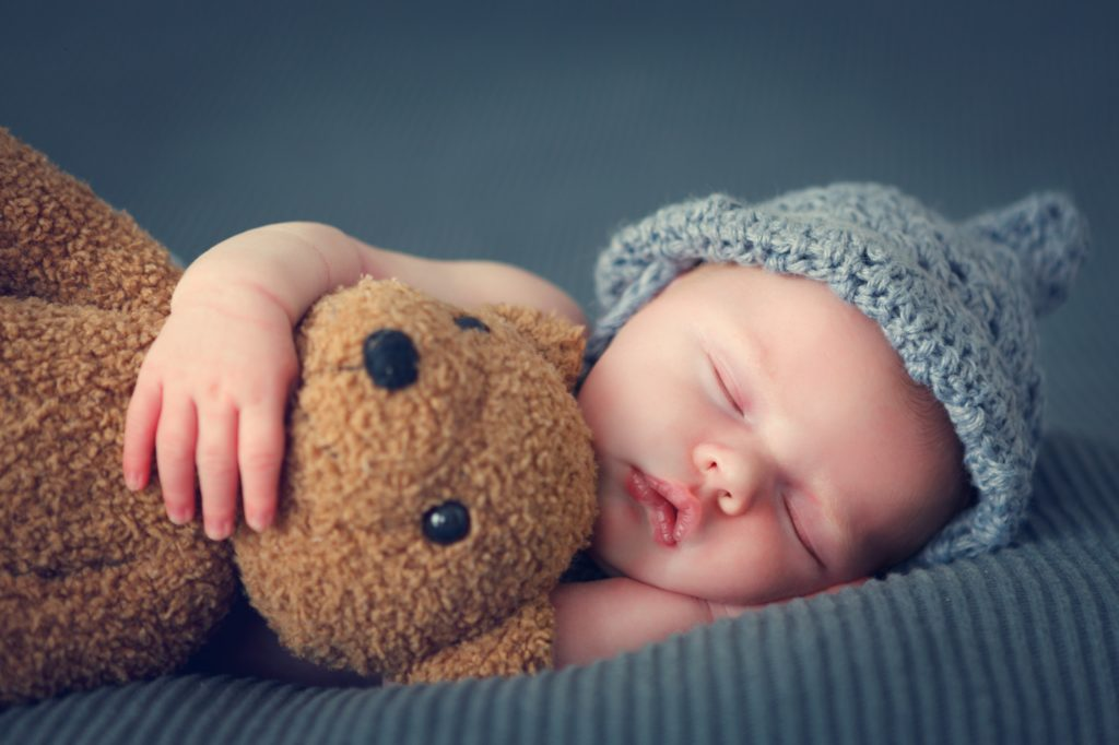 Baby schläft mit Teddybär im Arm