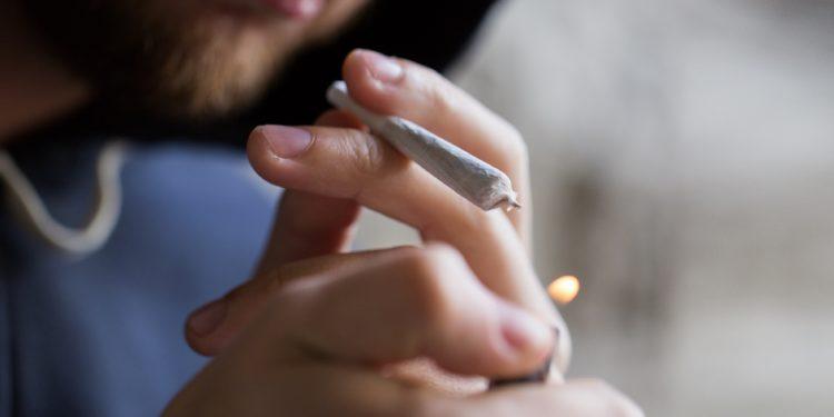 Mann raucht Cannabis.
