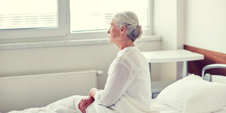 Ältere Frau sitzt auf einem Bett im Krankenhaus