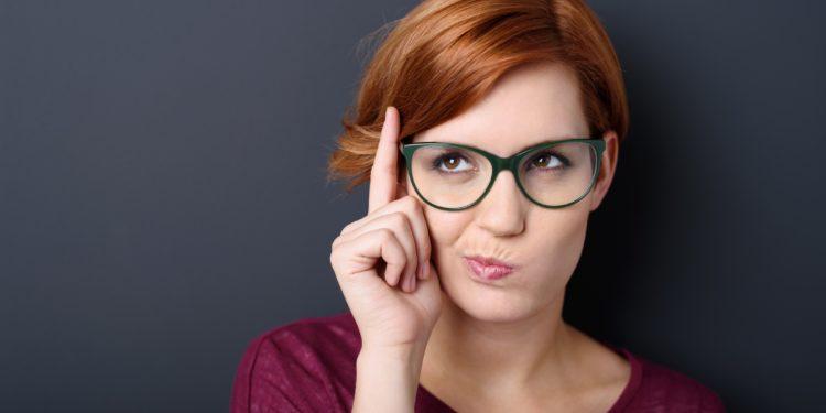 Frau mit Brille denkt nach fasst sich mit einem Finger an die Stirn