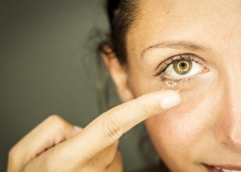 Frau entfernt Kontaktlinse aus dem Auge