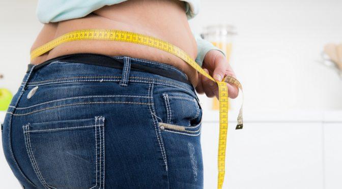 Übergewichtige Person misst Bauchumfang