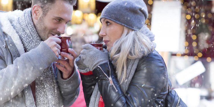 Ein Mann und eine Frau stehen im Schnee und trinken Glühwein.