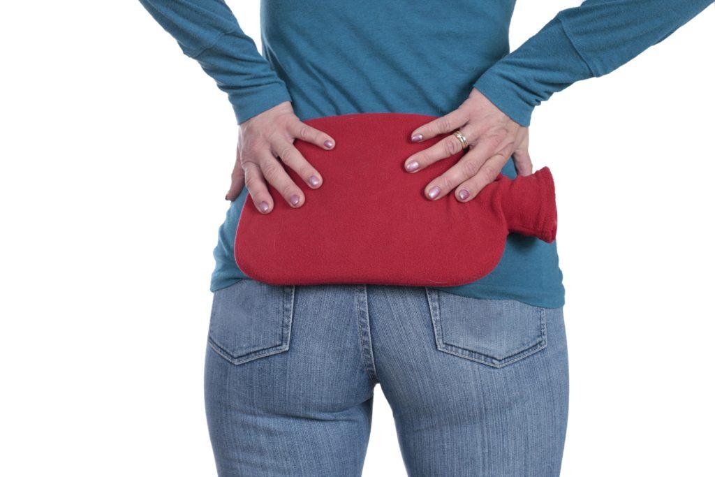 Frau hält Wäremkissen in ihren Rücken
