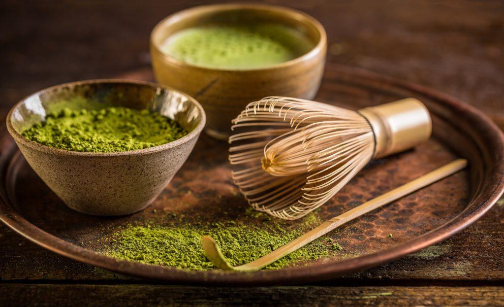 Matcha-Tee-Pulver sowie zubereiteter Matcha-Tee und ein Matcha-Besen auf einem Tablett