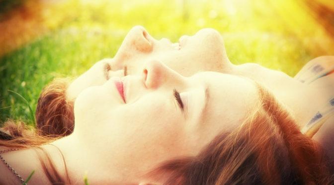 Zwei Menschen liegen bei Sonnenschein auf einer Wiese