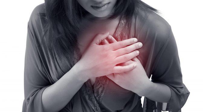 Frau fasst sich mit ihren Händen an den schmerzenden Brustkorb