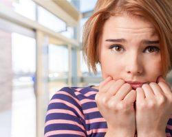 Verängstigte Frau hält sich ihre Fäuste an das Gesicht