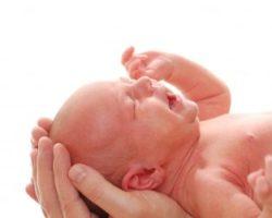 Baby weint in den Händen seiner Mutter