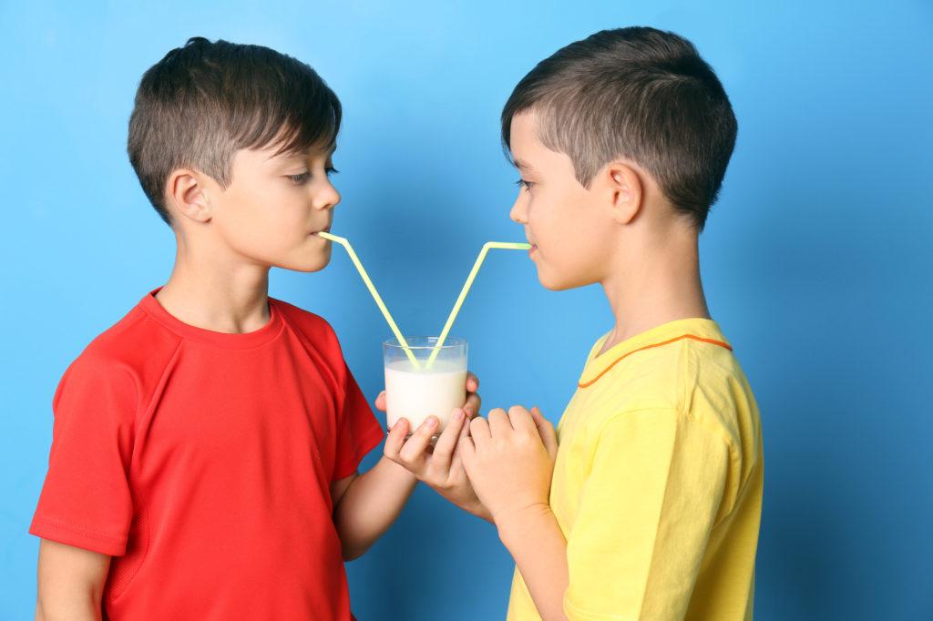 Zwillingsbrüder trinken mit Strohhalmen Milch aus einem gemeinsamen Glas
