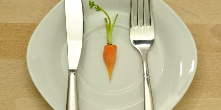 Eine kleine Möhre mit Messer und Gabel auf einem Teller
