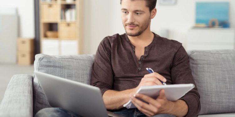 Mann mit Laptop macht sich auf einem Block Notizen