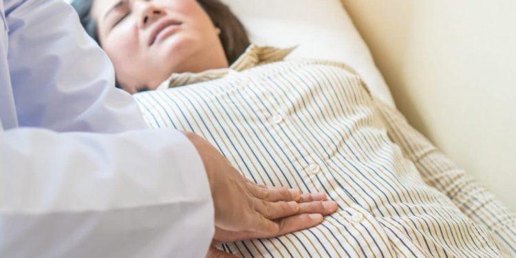 Frau leidet unter Schmerzen im Blinddarm.